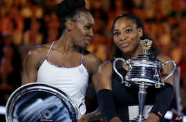United States' Serena Williams, right, holds her trophy after defeating her sister Venus, left, during the women's singles final at the Australian Open tennis championships in Melbourne, Australia, Jan. 28, 2017.