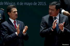 Mexico's President Enrique Pena Nieto (L) applauds with Mexico Interior Minister Miguel Angel Osorio Chong during a ceremony to sign into law a new-anti corruption legislation, at the National Palace in Mexico City, May 4, 2015.