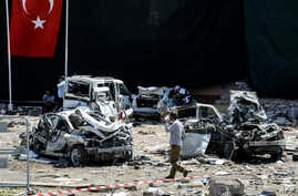 A man walks among the wreckage of vehicles as Turkish rescue workers and police inspect the blast scene following a car bomb attack on a police station in the eastern Turkish city of Elazig, Aug. 18, 2016.