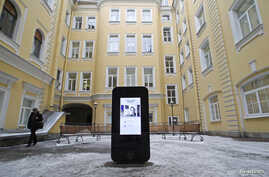 A man walks past a recently erected iPhone-shaped monument in memory of Apple's late co-founder Steve Jobs in the yard of the State University of Information Technologies, Mechanics and Optics, St. Petersburg, January 10, 2013.