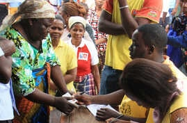 Voters produce identity documents as they go through the voting process at a polling station, in Maputo, Mozambique, Oct. 15, 2014.