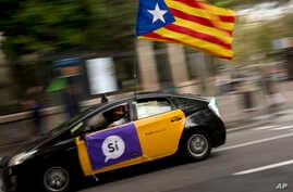 A man drives his taxi decorated with an estela flag and publicity supporting the Oct. 1 vote in Barcelona, Spain Friday, Sept. 22, 2017.