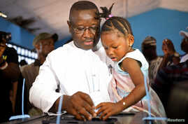 Julius Maada Bio, the presidential candidate for the Sierra Leone People's Party (SLPP), carries his daughter as he casts his vote during a presidential run-off in Freetown, Sierra Leone, March 31, 2018.