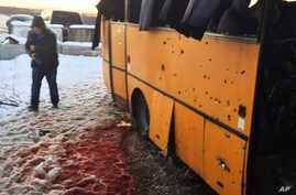 In this photo provided by the Ukrainian Interior Ministry, a man walks past snow covered with blood as he passes by a bus destroyed by a rebel shell at the checkpoint near the town of Volnovakha in the Donetsk region, eastern Ukraine, Jan. 13, 2015.