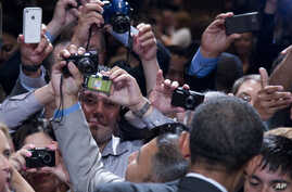 Members of the audience take photographs as President Barack Obama shakes hands at The National Association of Latino Elected and Appointed Officials' Annual Conference at the Walt Disney World Resort in Florida, June 22, 2012.