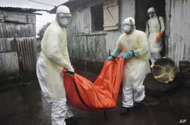 Health workers in protective gear carry the body of a woman suspected to have died from Ebola virus, from a house in New Kru Town at the outskirt of  Monrovia, Liberia, Oct. 8, 2014.
