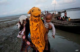 In this Sept. 21, 2017 photo, a Rohingya woman carries a child after crossing a stream on a small boat near Cox's Bazar's Dakhinpara area,