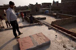 Relatives stand on the terrace of a house where a 15-year-old girl was set on fire after being raped at Tigri village, near Noida, a suburb of New Delhi, India. Police on Wednesday said that girl who was raped and set on fire this week has died in th