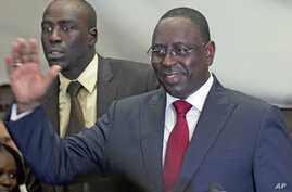 Senegalese opposition presidential candidate Macky Sall (R) celebrates at a news conference in Dakar, Senegal, March 25, 2012.