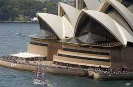 A loan boat decorated with national flags sails past the Opera House in Sydney, Australia (File Photo)