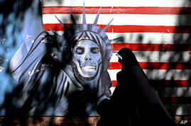 FILE - An Iranian woman walks past graffiti art characterizing the U.S. Statue of Liberty, painted on the wall of the former U.S. Embassy in Tehran, Iran, Sept. 25, 2007. An Iranian-American businessman and his father, who are serving 10-year prison