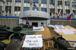 Anti-Western signs are seen on the barricades set up in front of a government building seized by pro-Russia separatists in Luhansk, eastern Ukraine, April 10, 2014.