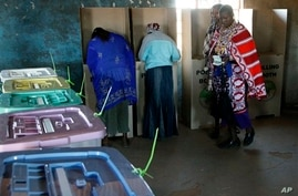 A Masai woman walks towards ballot boxes to cast her vote in a general election in Kajiado West, some 60 kilometers (37 miles) from Nairobi, Kenya, Monday, March 4, 2013.