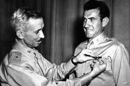 In this 1942 file photo, Brig. Gen. Isaiah Davics, commander of the Army Flying School in Midland, Texas, pins silver bombardier wings on Lt. Louis Zamperini.