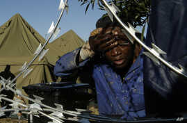 A man washes his face outside a shelter for displaced foreigners in east of Johannesburg, South Africa, April 21, 2015.