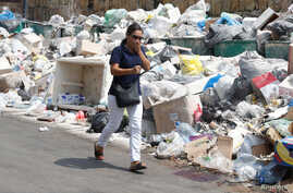 A woman covers her nose as she walks past garbage piled up along a street in Dekwaneh area, Mount Lebanon, Aug. 29, 2016.
