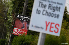 Anti-abortion rights and pro-abortion rights posters are seen outside the home of Amy Callahan, who received a fatal fetal diagnosis at 12 weeks into her pregnancy and traveled to Liverpool for a termination in Dublin, Ireland, May 7, 2018. Ireland w