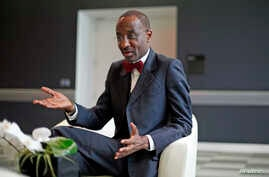 FILE - Nigeria's central bank governor Sanusi Lamido Sanusi gestures during an interview with Reuters in London.