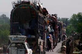 People fleeing the military offensive against the militants in North Waziristan, travel atop a vehicle with their belongings while entering Bannu, located in Pakistan's Khyber-Pakhtunkhwa province, June 20, 2014.