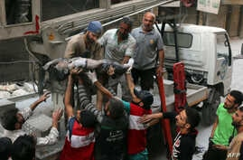 Syrian civil defense volunteers, known as the White Helmets, pass the body of a boy after he was pulled from the rubble following a government forces air strike on the rebel-held al-Shaer neighbourhood of the northern Syrian city of Aleppo, Sept. 27,...