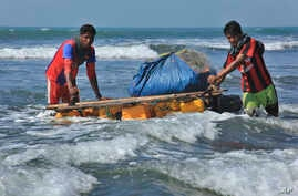 Rohingya fishermen pull their raft made of empty plastic containers along the coastline of the Bay of Bengal in Tha Pyay Taw village, Maungdaw, western Rakhine state, Myanmar, Jan. 16, 2017..