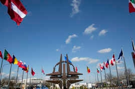 FILE - NATO symbol and flags of the NATO nations outside NATO headquarters in Brussels.