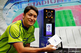 NEC Green Rockets' rugby player Teruya Goto poses with the face recognition system for Tokyo 2020 Olympics and Paralympics, which is developed by NEC corp, during its demonstration in Tokyo, Japan, Aug. 7, 2018.