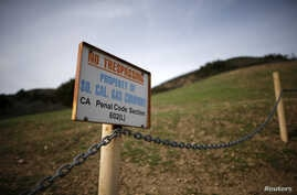 FILE - A gas company sign marks a fence near the site of the Aliso Canyon storage field where gas has been leaking in Porter Ranch, California, Jan. 21, 2016.