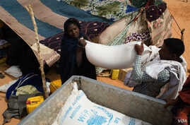 A recently arrived refugee from Mali is helped to load her rations of rice, oil and sugar onto a pick-up at the M'Berra refugee camp for Malian refugees in southeastern Mauritania, March 2, 2013. (Nyani Quarmyne/MSF)