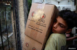 A boy unloads aid parcels in the rebel-held besieged town of Zamalka, in the Damascus suburbs, Syria June 29, 2016. Picture taken June 29, 2016.