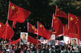 Demonstrators holding posters of China's late Chairman Mao Zedong, Chinese national flags and banners march past riot policemen during a protest on the 81st anniversary of Japan's invasion of China, outside the Japanese embassy in Beijing, September