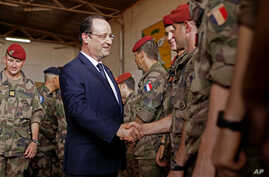 French president Francois Hollande, front left, greets French troops as he arrives at the French military operation headquarters at M'Poko airport in Bangui, Central African Republic, Feb. 28, 2014.