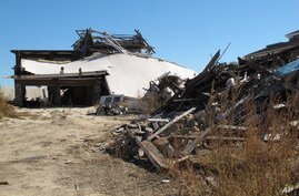The ruins of an oceanfront home destroyed by Superstorm Sandy is scattered next to an existing home in Mantoloking N.J.,  Tuesday,  Oct. 15, 2013.   Mantoloking will vote Wednesday morning to carry out a reassessment of all taxable properties for the