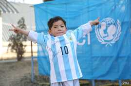 Murtaza Ahmadi posing with a jersey sent to him by Argentine football star Lionel Messi.
