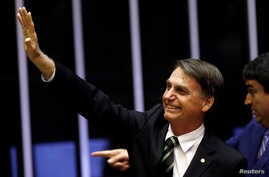 Brazil's President-elect Jair Bolsonaro waves during a session at the National Congress in Brasilia, Brazil, Nov. 6, 2018.