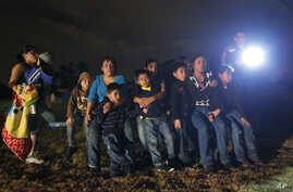 FILE - A group of young migrants from Honduras and El Salvador who crossed the U.S.-Mexico border illegally are stopped in Granjeno, Texas, June 25, 2014..