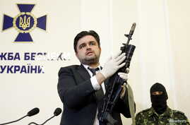 Markian Lubkivskyi, adviser of Ukraine's Security Service (SBU), shows a Kalashnikov automatic rifle with grenade launcher seized from a man identified by SBU as one of two Russian servicemen recently detained by Ukrainian forces, in Kyiv, Ukraine, M