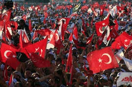 FILE - In this Sunday, July 9, 2017, photo, supporters of Kemal Kilicdaroglu, the leader of Turkey's main opposition Republican People's Party, hold Turkish flags in Istanbul, as they gather for a rally following their 425-kilometer (265-mile) 'March