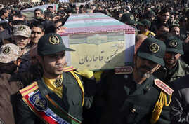 FILE - Civilians and armed forces members carry the flag-draped coffins of Iranian Revolutionary Guard Gen. Mohsen Ghajarian, foreground, and five soldiers who were killed in fighting in Syria, during their funeral outside the headquarters of the gua