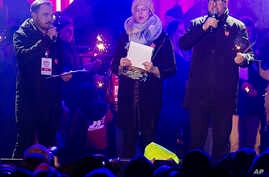 Gdansk Mayor Pawel Adamowicz, right, speaks to an audience at a charity event shortly before he was stabbed in Gdansk, Poland, Jan. 13, 2019.
