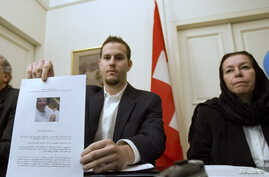 FILE - Christine Levinson (right), wife of former FBI agent Robert Levinson, watches as her son Daniel Levinson displays a web print of his father's picture to journalists while attending a news conference at Switzerland's embassy in Tehran, Dec. 22,