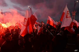 FILE - Demonstrators burn flares and wave Polish flags during the annual march to commemorate Poland's National Independence Day in Warsaw, Poland, Nov. 11, 2017.