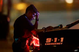 A Dallas police officer, who did not want to be identified, takes a moment as she guards an intersection in the early morning after a shooting in downtown Dallas on July 8, 2016.