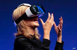 British television presenter Rachel Riley shows a virtual-reality headset called Gear VR during an unpacked event of Samsung ahead of the consumer electronic fair IFA in Berlin, Wednesday, Sept. 3, 2014.