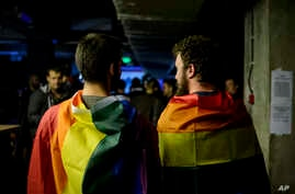 Two men draped in rainbow flags are seen in a nightclub in Bucharest, Romania, Oct. 7, 2018, following a referendum on marriage which was voided due to low voter turnout.