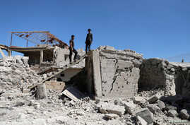 FILE - Men inspect a damaged house in Busra al-Harir, near Deraa, Syria, March 13, 2018. Russian jets struck the opposition-held town on June 24, 2018, opposition sources said.