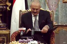 Yemeni President Ali Abdullah Saleh signs a document agreeing to step down after a long-running uprising to oust him from 33 years in power in Riyadh, Saudi Arabia, Nov. 23, 2011.
