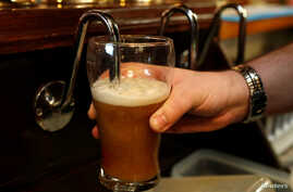 FILE - A barman pulls a pint of beer in a pub in Liverpool, northern England.