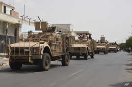 Yemeni fighters against Shiite rebels ride military vehicles on a street in the port city of Aden, July 14, 2015.