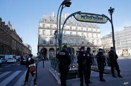 FILE -Police officers stand on patrol at a Metro station outside the Louvre museum near where a soldier opened fire after he was attacked in Paris, Feb. 3, 2017.